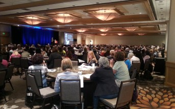 A picture of conference participants watching and listening to the keynote address.
